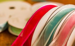 Close up of rolls of colorful cloth tape, over a wooden table in a blurred background.  Royalty Free Stock Photos