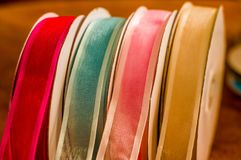 Close up of rolls of colorful cloth tape, over a wooden table in a blurred background.  Royalty Free Stock Image