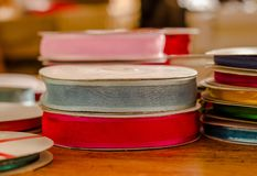 Close up of rolls of colorful cloth tape, red and gray over a wooden table in a blurred background.  Stock Photography