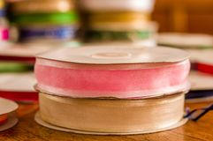 Close up of rolls of colorful pink and white cloth tape, over a wooden table in a blurred background.  Stock Photography