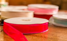 Close up of rolls of colorful red cloth tape, over a wooden table in a blurred background.  Royalty Free Stock Images