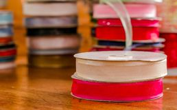 Close up of rolls of colorful white and red cloth tape, over a wooden table in a blurred background.  Royalty Free Stock Images