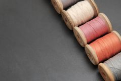 Close up Rolls of Vintage Colorful Threads. Clothes Repair, Black Dark Background. Sewing work process. copy Space. Close up Rolls of Vintage Colorful Threads stock images
