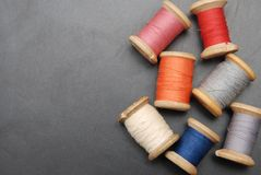 Close up Rolls of Vintage Colorful Threads. Clothes Repair, Black Dark Background. Sewing work process. copy Space. Close up Rolls of Vintage Colorful Threads stock photos