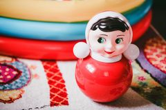 Close up roly-poly toy for children. Close-up of bright red tumbler toy on floor in children`s room Royalty Free Stock Photography