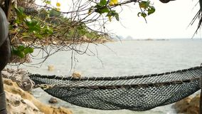 Close up of romantic cozy empty hammock with tropical ocean on the background. Vacation to paradise, travel to the sea. Holiday in exotic beach resort, idyllic stock footage