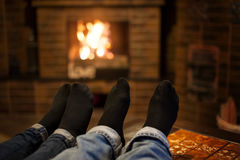 Close up of romantic legs in socks in front fireplace Stock Images