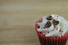 Valentines day romantic cup cake with white buttercream and a small wooden love heart decorations on top with space. Close up romantic valentine day food of a stock photo