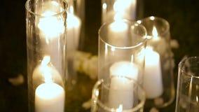 Close-up Romantische brandende witte kaarsen in glasvazen die zich op een gras voor een ceremonie van het avondhuwelijk bevinden stock videobeelden