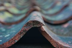 Roof tiles on old house closeups. Close-up of roof boilers on old house, pictures on time to renovate, companies selling home goods. Macro photo, color neutral royalty free stock photography