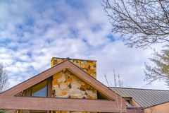 Close up of the roof of a house against trees and sky with cottony clouds. A colorful chimney protrudes from the roof of this house royalty free stock image