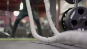 Close-up of rope for a crossfit, with which a man exercises in the gym. Male athlete on floor beats sports equipment to develop endurance and strength stock footage