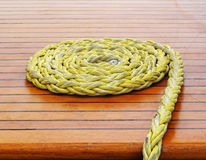 Close-up of a rope with a knotted end tied around a cleat on a w Royalty Free Stock Photo