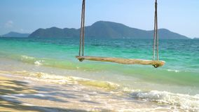 Close-up of a rope swing hanging on the beach with turquoise water. Close-up of a rope swing hangs on a beautiful beach with white sand and turquoise water stock video