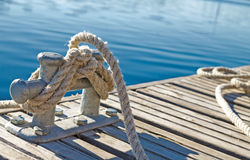 Close up of rope tied up on a bitt on wooden dock. Blue water in the background Royalty Free Stock Images