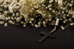 Close up of a rosary beads with a black cross in blurred white small flowers, black background Stock Photos