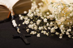 Close up of a rosary beads over a holy bible with blurred white small flowers, black background Stock Image