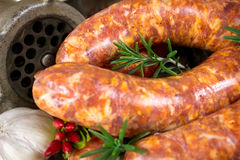 Close-up of rosemary on raw sausages and meat grinder Stock Photo