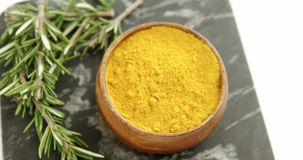Rosemary with turmeric powder in bowl 4k. Close-up of rosemary with turmeric powder in bowl 4k stock video