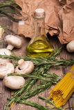A close-up of rosemary twigs, yellow uncooked pasta, mushrooms, and olive oil. Fresh ingredients on a wooden table Stock Photography