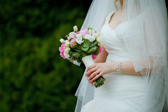 Close-up of roses wedding bouquet in a hands of a slim bride in Royalty Free Stock Images