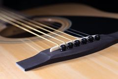 Parts of acoustic guitar close-up. Close-up of rosette and strings of the acoustic guitar on black background Stock Photography