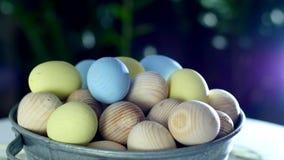 Close-up, rotação, a composição festiva da Páscoa nos raios de luz, em uma palha, em uma bacia do metal, muitos coloridos
