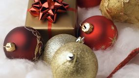 Close up of rotating baubles and gift box on cotton wool stock footage
