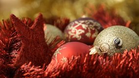 Close up of rotating gold baubles on christmas decoration with wind effect stock footage