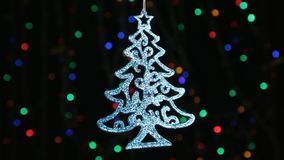 Close-up, rotation of a blue Christmas tree hanging on a silver rope. Christmas and New Year decoration. Abstract blurred bokeh holiday background. Blinking stock footage