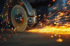 Close-up of the rotation of the disk angle grinder during operation. Bright sparks from metal cutting. Dark industrial background stock photography