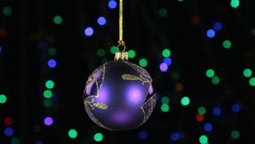 Close-up, the rotation of a lilac Christmas ball hanged on a golden rope. Christmas and New Year decoration. Abstract blurred bokeh holiday background stock footage