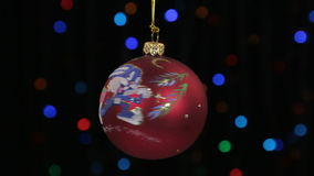 Close-up, the rotation of a red Christmas ball hanged on a golden rope. Christmas and New Year decoration. Abstract blurred bokeh holiday background. Blinking stock footage