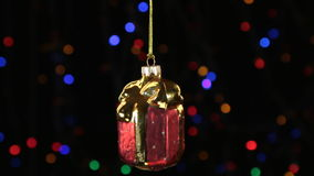 Close-up, the rotation of a red Christmas gift hanged on a golden rope. Christmas and New Year decoration. Abstract blurred bokeh holiday background. Blinking stock video