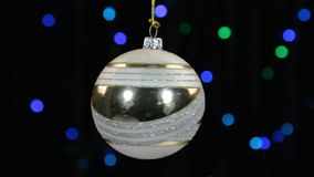 Close-up, the rotation of a white Christmas ball hanged on a golden rope. Christmas and New Year decoration. Abstract blurred bokeh holiday background stock video footage