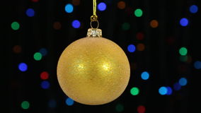 Close-up, the rotation of a yellow Christmas ball hanged on a golden rope. Christmas and New Year decoration. Abstract blurred bokeh holiday background stock video