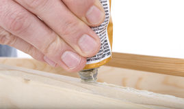 Close Up Rough Hand Squeezing Wood Glue. On Cabinet Royalty Free Stock Photo