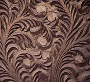Close-up of rough wood carving. Close-up of area of crudely carved old brown wooden door with pattern of leaves and swirls in high relief Royalty Free Stock Photography
