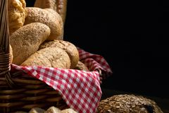 Close up of round bun bread in the basket. On black background Stock Image
