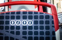 Close up of round icon priority seat for elderly, pregnant or disabled people on a bus seat in Barcelona. Brcelona public transport, close up of round icon royalty free stock photo