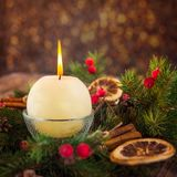 Close up round ivory burning Christmas candle on advent wreath with natural decor on the old rustic table with blurred luminous ba Stock Photography