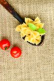 Raw farfalle. Close up of  row farfalle pasta on  black slate .wirh cherry tomatoes and fresh basil .Italian healthy food background. View from above Stock Image