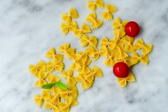 Raw farfalle. Close up of  row farfalle pasta on   marble slate .wirh cherry tomatoes and fresh basil .Italian healthy food background. View from above Stock Photos