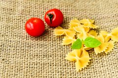 Raw farfalle. Close up of  row farfalle pasta on   marble slate .wirh cherry tomatoes and fresh basil .Italian healthy food background. View from above Stock Images