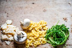 Italian   pasta ingredients. Close up of  row farfalle pasta , parmesan cheese, fresh parsley   and  mushrooms .spaghetti and ingredients. Italian healthy food Royalty Free Stock Photo