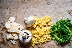Italian   pasta ingredients. Close up of  row farfalle pasta , parmesan cheese, fresh parsley   and  mushrooms .spaghetti and ingredients. Italian healthy food Stock Image