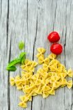 Raw farfalle. Close up of  row farfalle pasta on   wooden background  .wirh cherry tomatoes and fresh basil .Italian healthy food background. View from above Stock Images