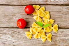Raw  farfalle. Close up of  row farfalle pasta on    wooden  background  .wirh cherry tomatoes and fresh basil .Italian healthy food background. View from above Royalty Free Stock Photo