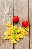 Raw farfalle. Close up of  row farfalle pasta on   wooden background .wirh cherry tomatoes and fresh basil .Italian healthy food background. View from above Royalty Free Stock Images