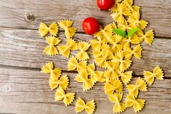 Raw farfalle. Close up of  row farfalle pasta on   wooden background  .wirh cherry tomatoes and fresh basil .Italian healthy food background. View from above Stock Image